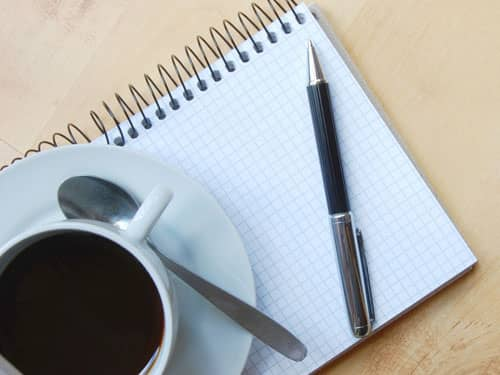 Notebook pen cup of coffee