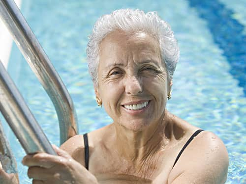 senior woman in a swimming pool, smiling