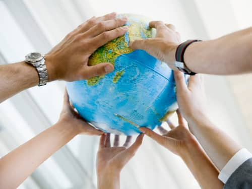Many hands touching globe