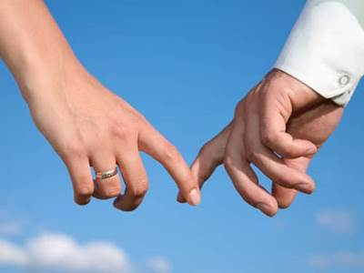 Couple's fingers touching against a blue sky