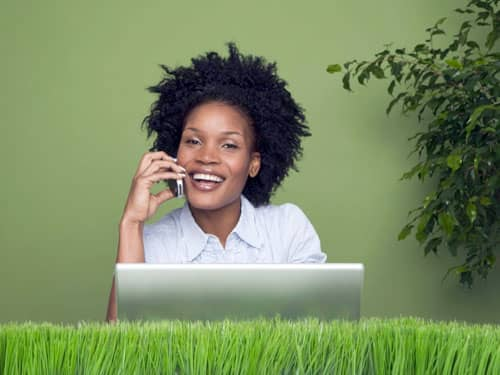 woman on phone with laptop on desk made of grass