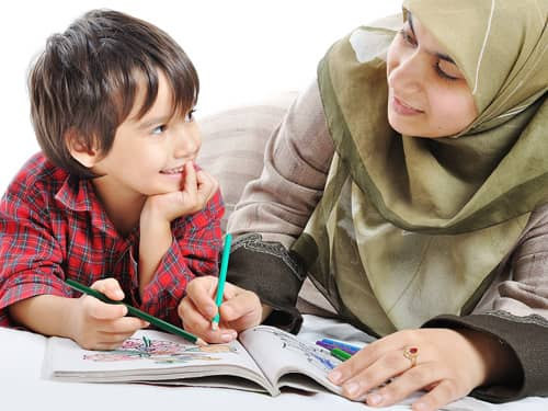 Muslim mother teaching son from coloring book