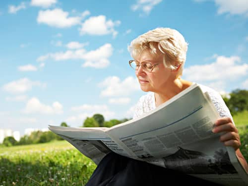 Woman reading the newspaper in a field
