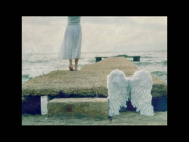 Woman walking on pier with white angel wings