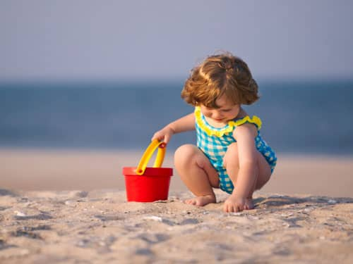 Little girl playing with beach sand