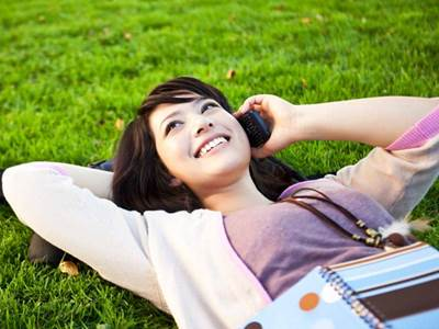 teen-girl-on-grass-cellphone