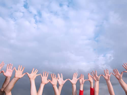 Group of hands reaching up to the sky.