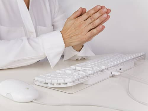 Praying Hands Over a Computer a Keyboard