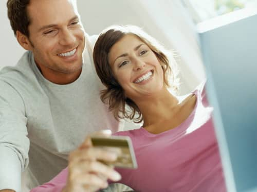 Couple using credit card to buy online