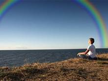 Meditating woman by canyon with a rainbow in the sky