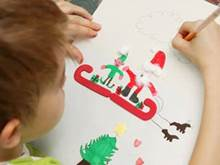 Child drawing Santa and an elf on a sleigh