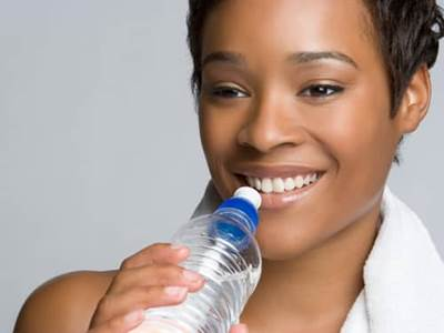Exercising woman drinking water