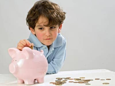 Talking to kids about the economy, boy with piggy bank