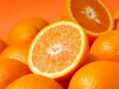 Bright Halved Oranges, on top of whole oranges