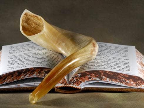 A shofar resting upon a hebrew book