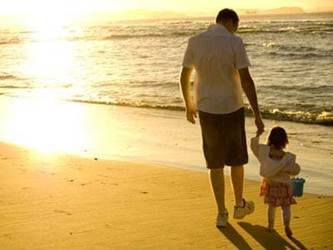 Father walking with daughter on a beach