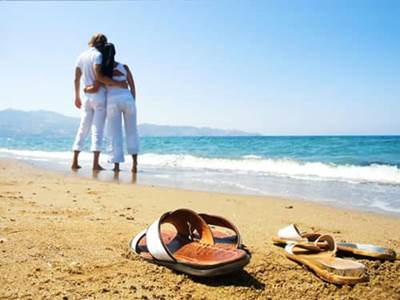 Sandals and couple on sandy beach