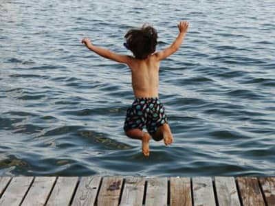 Boy Jumping into water from dock