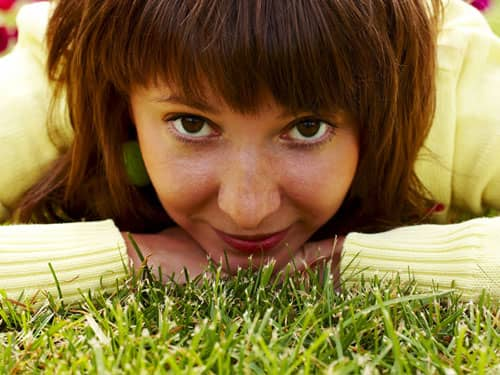Woman staring up from the grass