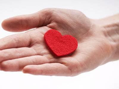 Hand holding a heart shaped trinket