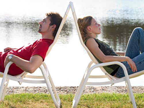 Couple in lawn chairs by lake