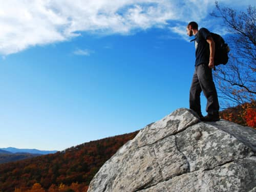 Man standing on rock looking over landscape
