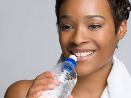 Exercising woman drinking water