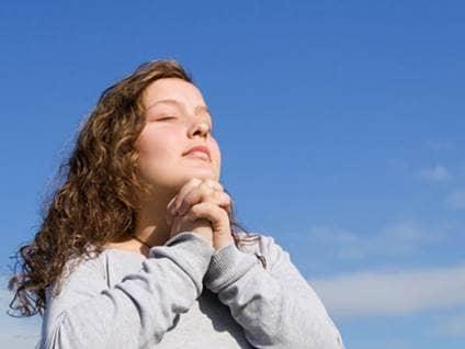 Woman praying against blue sky