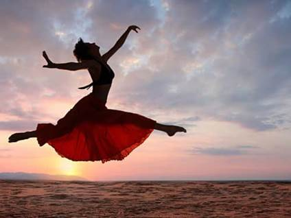 Woman dancing in desert against sunset