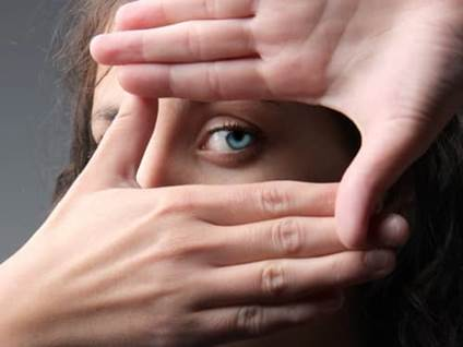 Woman peeking through hands