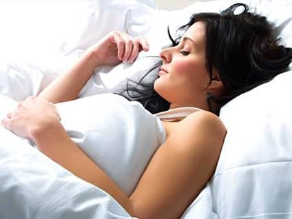 Woman sleeping on white sheets in bed