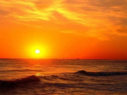 Orange sun setting on the ocean horizion