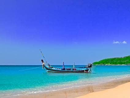 Boat on a coastal island beach against a blue sky